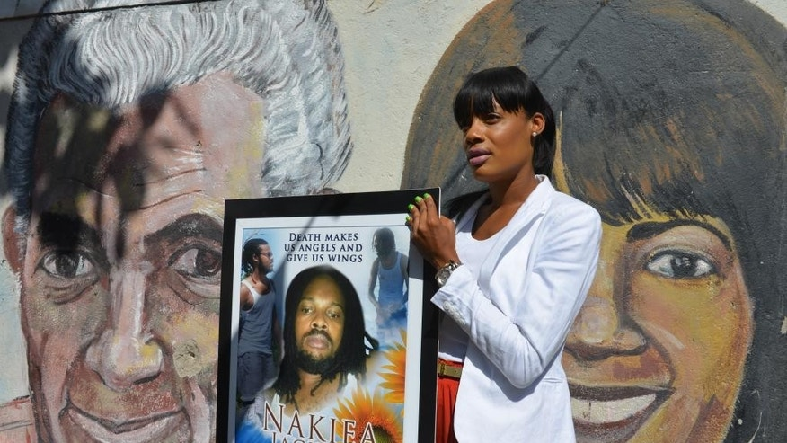 "In this April 16, 2014, photo, Shackelia Jackson-Thomas holds a poster showing her brother, Nakiea Jackson, just outside his small ""cookshop"" in the Orange Villa section of Jamaica's capital of Kingston. Earlier this year, the 27-year-old cook was shot dead by a policeman as pots of curried goat simmered on the stove of his kitchen, the exterior of which is decorated with murals of past and present political leaders. The patrolman who shot him is one of 27 police officers now facing charges of murder brought by an investigative commission probing allegations against police and soldiers. Jamaica's security forces have long been accused of indiscriminate shootings and unlawful killings. (AP Photo/David McFadden)"