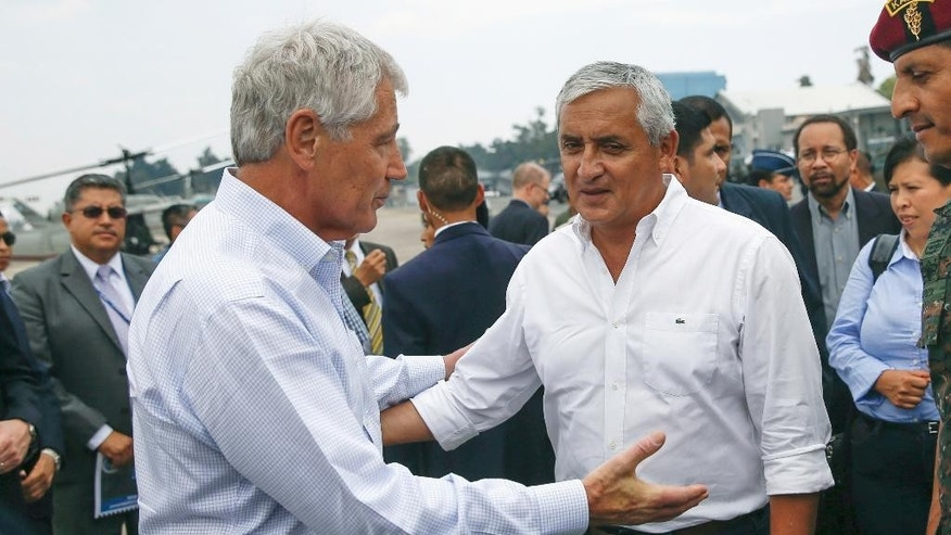 Defense Secretary Chuck Hagel and Guatemalan President Otto Perez Molina embrace before his departure from Guatemala City, Guatemala, Friday, April 25, 2014.    (AP Photo/Shannon Stapleton, Pool)