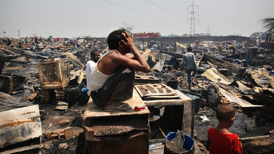 An Indian man wails as he sits amidst the remains of his home after a fire in a slum in New Delhi, India, Friday, April 25, 2014. A massive fire ripped through a New Delhi slum Friday, destroying nearly 500 thatched huts and leaving already impoverished families homeless, said a fire department official. Seven people were hospitalized with minor burn wounds. (AP Photo/Manish Swarup)