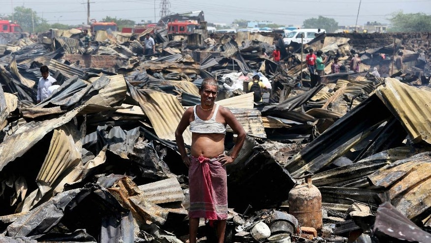 An Indian man stands at the site of his home as he watches the devastation around him after a fire in a shanty town in New Delhi, India, Friday, April 25, 2014. A massive fire ripped through a New Delhi slum Friday, destroying nearly 500 thatched huts and leaving already impoverished families homeless, said a fire department official. Seven people were hospitalized with minor burn wounds. (AP Photo/Manish Swarup)
