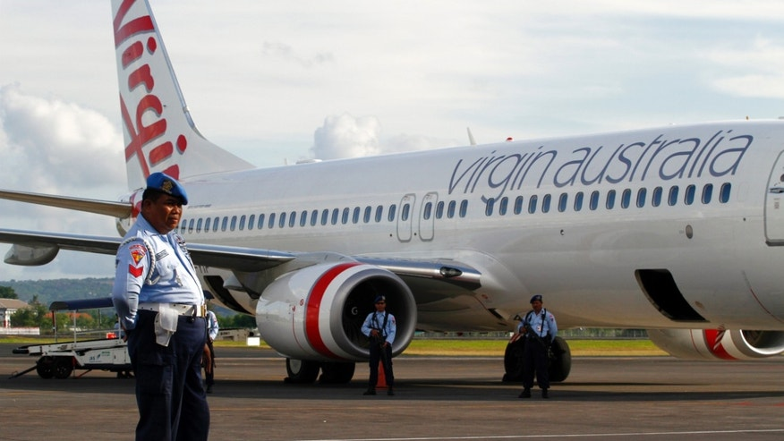 April 25, 2014 - Indonesian Air Force personnel stand guard by a Virgin Australia airplane in Bali, Indonesia. A drunken passenger who caused a hijack scare on a Virgin Australia flight by trying to break into the cockpit was arrested Friday after the plane landed on Bali, officials said.