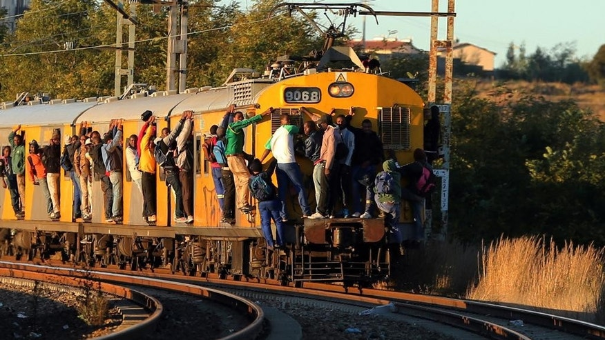 "In this photo taken on Thursday, April 24, 2014, commuters hang on to a moving passenger train in Soweto, south of Johannesburg, South Africa. As South Africa marks the 20th anniversary of multiracial democracy on Sunday, April 27, the achievements and soaring expectations of what was dubbed a ""rainbow nation"" have been tempered by a different inequality - the yawning gulf between rich and poor. (AP Photo/Themba Hadebe)"