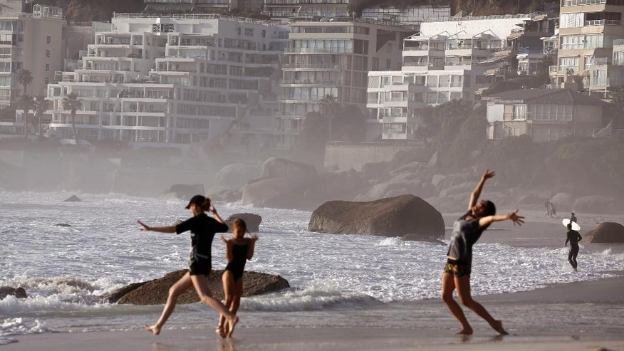 In this photo taken on Saturday, April 19, 2014, children play on the beach at Clifton, a white-only area during the Apartheid era, near the city of Cape Town, South Africa. As South Africa marks the 20th anniversary of multiracial democracy on Sunday, April 27 and despite notable gaps in service, it has delivered housing, water and electricity to millions since 1994 and boasts a widely admired constitution and an active civil society, but struggles with high unemployment, one of the world's highest rates of violent crime and is still working through issues of race and identity. (AP Photo/Schalk van Zuydam)