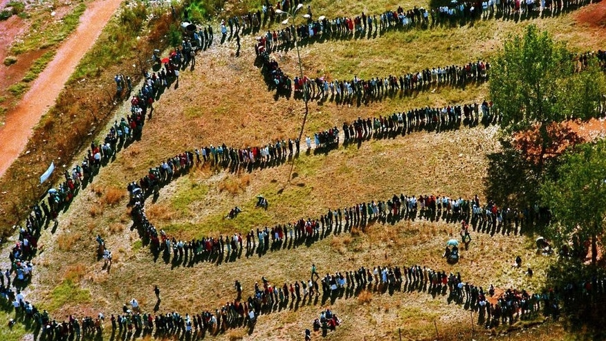 "FILE - In this Wednesday, April 27, 1994 aerial file photo, people queue outside a polling station to cast their votes in the nation's first all-race elections in the Soweto, township, southwest of Johannesburg, South Africa. As South Africa marks the 20th anniversary of multiracial democracy on Sunday, April 27 the achievements and soaring expectations of what was dubbed a ""rainbow nation"" have been tempered by a different inequality - the yawning gulf between rich and poor. (AP Photo/Denis Farrell, File)"