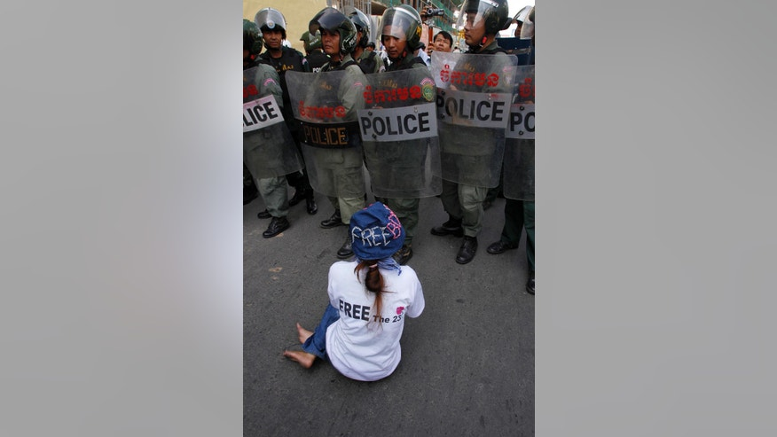 A woman from Boeung Kak Lake community sits in front of a line of local security guards near a blocked main street near the Phnom Penh Municipality Court during villagers' gathering to call for the release of anti-governments protesters who were arrested in a police crackdown, in Phnom Penh, Cambodia, Friday, April 25, 2014. Almost two dozen Cambodian factory workers and rights activists have gone on trial in connection with labor protests earlier this year that rocked Prime Minister Hun Sen's government. (AP Photo/Heng Sinith)