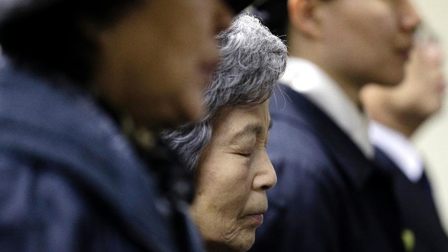 Kyungsook Kwon prays for the victims of the sunken South Korean ferry Sewol during a temporary memorial at the Korean-American association center in Chicago, Thursday, April 24, 2014. The Sewol sank last week on a routine trip from the port of Incheon, near Seoul, to the southern island of Jeju. Of the 476 passengers and crew on board, 339 were children and teachers on a high school outing. (AP Photo/Nam Y. Huh)