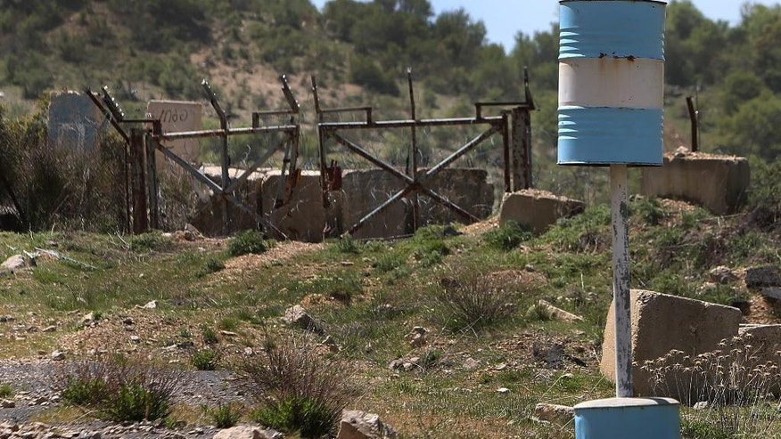 In this picture taken on Wednesday April 16, 2014, barrels marking the Blue Line, a U.N.-drawn boundary between Lebanon and Israel, are seen set in front of a damaged Israeli gate where Hezbollah captured three Israeli soldiers in 2000, at the barbed wire that separate Lebanon and Israeli-occupied Chebaa farms, southeast Lebanon. This small, scenic patch of land where the frontiers of Syria, Lebanon and Israel meet holds the Middle East's most explosive issues. With Syria's conflict, raging into the fourth year, enemies come intimately close to one another in the 65 square-kilometer Chebaa farms area that for decades has been a source of friction, complicated by ownership disputes and Israeli occupation. (AP Photo/Hussein Malla)