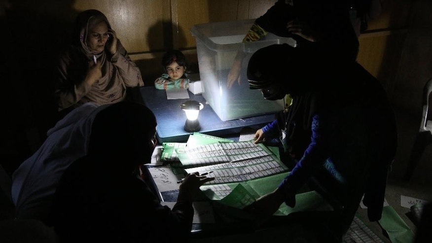 FILE - In this Saturday, April 5, 2014, file photo, Afghan election workers count ballots by the light of a lantern at a polling station in Jalalabad, east of Kabul, Afghanistan. Afghanistan is to release preliminary results in its crucial presidential election on Saturday, but the results are only one step in a potentially long road to determine who will succeed President Hamid Karzai. Neither Abdullah Abdullah, a former foreign minister, nor ex-finance minister Ashraf Ghani Ahmadzai look set to win a majority, meaning the violence-weary country could be heading for a runoff.  (AP Photo/Rahmat Gul, File)