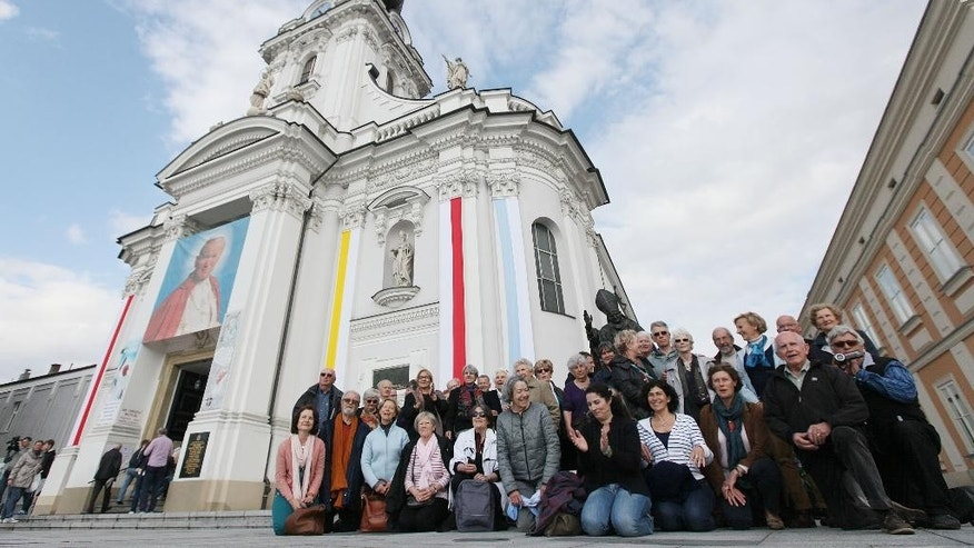 A group of pilgrims from near Avignon, France, take a picture by the figure of Pope John Paul II  in front of the basilica where he was baptized  in his hometown of Wadowice, Poland on Saturday, April 26, 2014,, on the eve of Poland's beloved pontiff being made a saint  in a Vatican ceremony.  Wadowice, and nearby Krakow are among the key places linked to John Paul in Poland that are holding observances to mark the occasion. The group will watch the Vatican ceremony live in Krakow.  (AP Photo/Czarek Sokolowski)