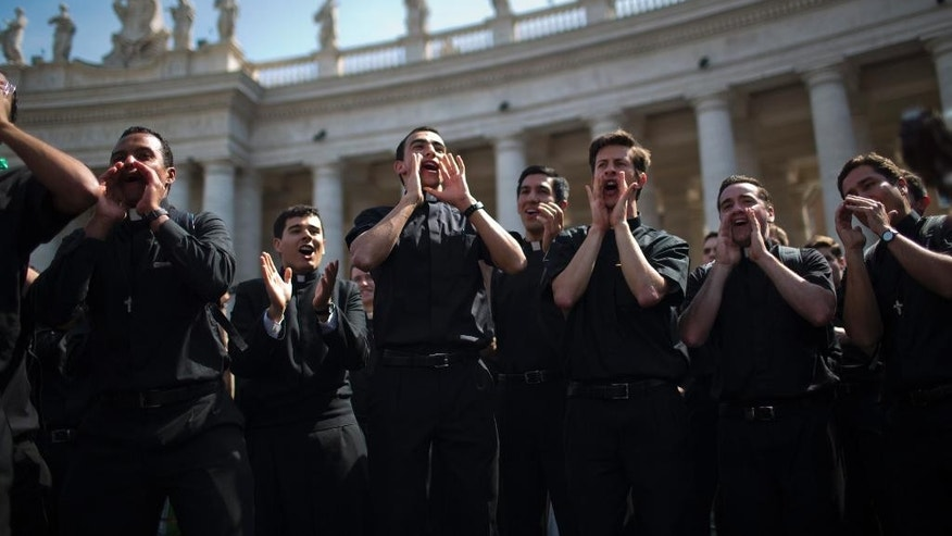 Priests sing and dance in St. Peter's Square at the Vatican, Saturday, April 26, 2014. Pilgrims and faithful are gathering in Rome to attend Sunday's ceremony at the Vatican where Pope Francis will elevate in a solemn ceremony John XXIII and John Paul II to sainthood. (AP Photo/Emilio Morenatti)