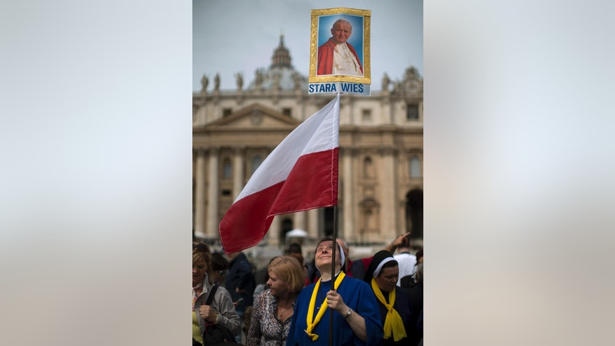 A Polish nun holds a portrait of late Pope Pope John Paul II in front of St. Peter's Basilica at the Vatican, Saturday, April 26, 2014. Pilgrims and faithful are gathering in Rome to attend Sunday's ceremony at the Vatican in which Pope Francis will elevate in a solemn ceremony John XXIII and John Paul II to sainthood. (AP Photo/Emilio Morenatti)
