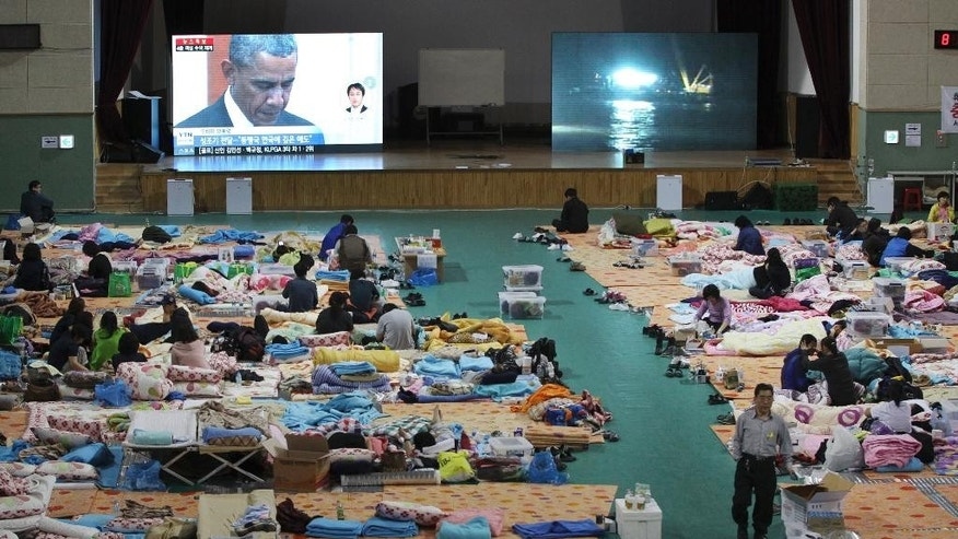 A TV screen shows U.S. President Barack Obama paying a silent tribute for the victims of South Korea's sunken ferry Sewol during a summit meeting with South Korean President Park Geun-hye as relatives of victims looks on at a gymnasium in Jindo, South Korea, Friday, April 25, 2014. As visiting Obama offered South Koreans his condolences Friday for the ferry disaster, the South Korean government conceded that some bodies have been misidentified and announced changes to prevent such mistakes from happening again. (AP Photo/Ahn  Young-joon)