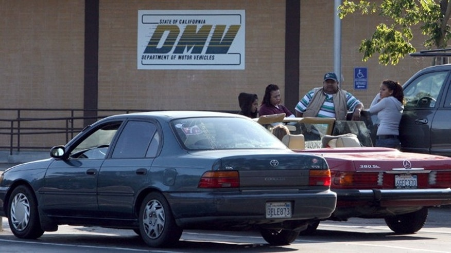 California Department of Motor Vehicles customers sit in the parking lot after finding out that the DMV is closed in Corte Madera, California. (Photo by Justin Sullivan/Getty Images)