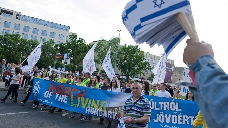 "Participants of the March of The Living walk along at Blaha Lujza square to commemorate victims of the Holocaust in Budapest, Hungary, Sunday, April 27, 2014. It marks the 70th anniversary of the beginning of the Hungarian holocaust during which some 600 thousand Jewish Hungarians were deported to Nazi death camps. The banner reads: ""About the past for the future"" (AP Photo/MTI, Bea Kallos)"