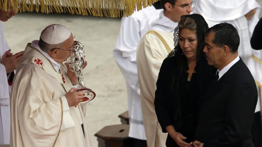 Pope Francis kisses the relic of Pope John Paul II she received from Floribeth Mora, second right, a Costa Rican woman whose inoperable brain aneurysm purportedly disappeared after she prayed to John Paul II, during a solemn ceremony in St. Peter's Square at the Vatican, Sunday, April 27, 2014. Pope Francis has declared his two predecessors John XXIII and John Paul II saints in an unprecedented canonization ceremony made even more historic by the presence of retired Pope Benedict XVI. (AP Photo/Gregorio Borgia)