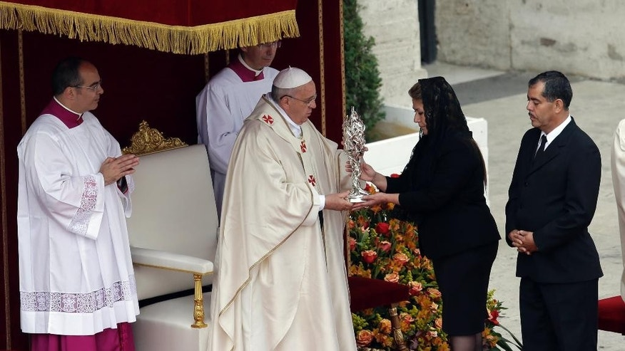 Pope Francis receives the relic of Pope John Paul II from Floribeth Mora, a Costa Rican woman whose inoperable brain aneurysm purportedly disappeared after she prayed to John Paul II, during a solemn ceremony in St. Peter's Square at the Vatican, Sunday, April 27, 2014. Pope Francis has declared his two predecessors John XXIII and John Paul II saints in an unprecedented canonization ceremony made even more historic by the presence of retired Pope Benedict XVI. (AP Photo/Alessandra Tarantino)