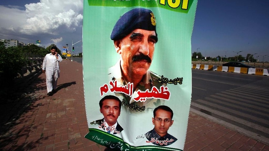 "A man walks past a banner showing a picture of Pakistan's Inter-Services Intelligence Chief Lt. General Zaheerul Islam, center, displayed by traders to show their support for the Pakistani army and ISI, in Islamabad, Pakistan, Saturday, April 26, 2014. The Pakistani army has formally filed a complaint seeking to shut down a leading private news channel over what the military calls ""false"" reports that the country's intelligence service shot one of its top anchors. (Anjum Naveed)"