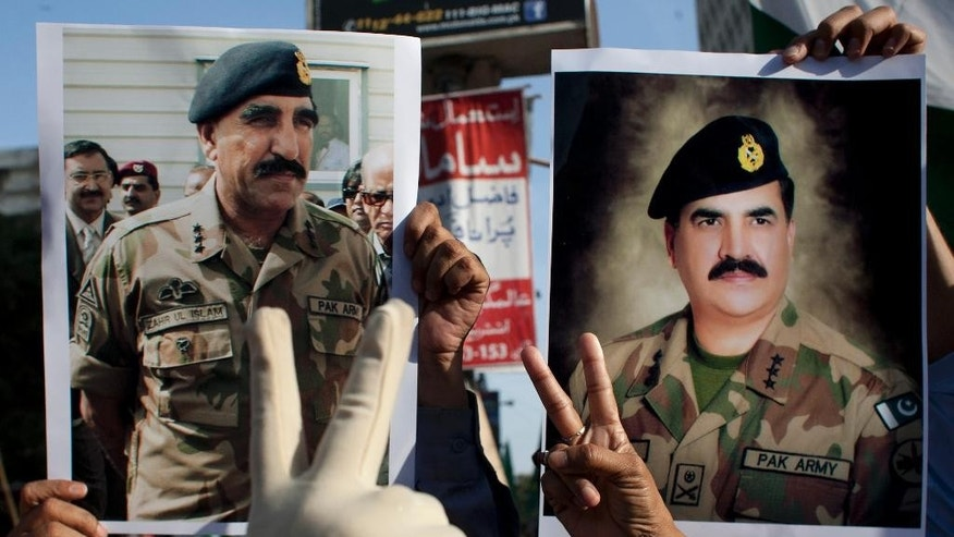 In this Friday, April 25, 2014 photo, Pakistan army supporters hold pictures of army chief Gen. Raheel Sharif, right, and Pakistan's Inter-Services Intelligence Chief Lt. General Zaheerul Islam at a rally in Karachi, Pakistan. A controversy has surfaced as Pakistan's powerful military faces off with the country's largest private television station over allegations that its forces were behind a shooting that seriously wounded Hamid Mir, one of its top anchors. But behind the chanting demonstrations and garish loyalty posters lies the deep challenge confronting Pakistan: Where does power lie in this country that's undergone three military coups since independence, with its army or its nascent civilian government? (AP Photo/Shakil Adil)