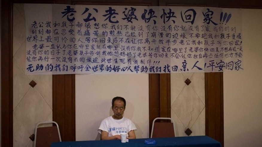 April 26, 2014: One of the relatives of Chinese passengers on board Malaysia Airlines Flight 370 sits underneath a banner written with messages dedicated to passengers on the missing plane during a briefing held by Malaysian officials at a hotel in Beijing, China. (AP Photo/Andy Wong)