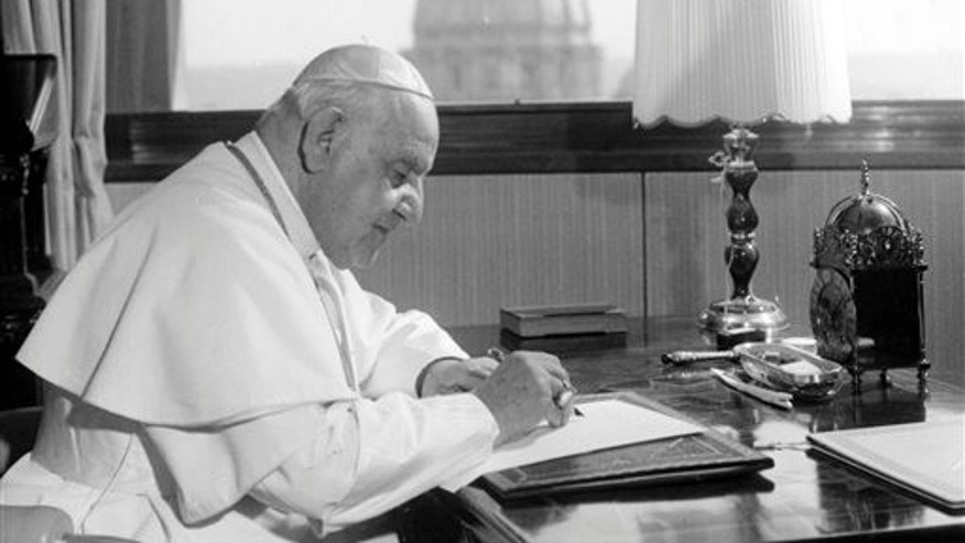 FILE - In this April 15, 1963 file photo, Pope John XXIII sits at his working desk in his studio in a 9th century tower in the Vatican gardens. In the background, the dome of St. Peter's Basilica.