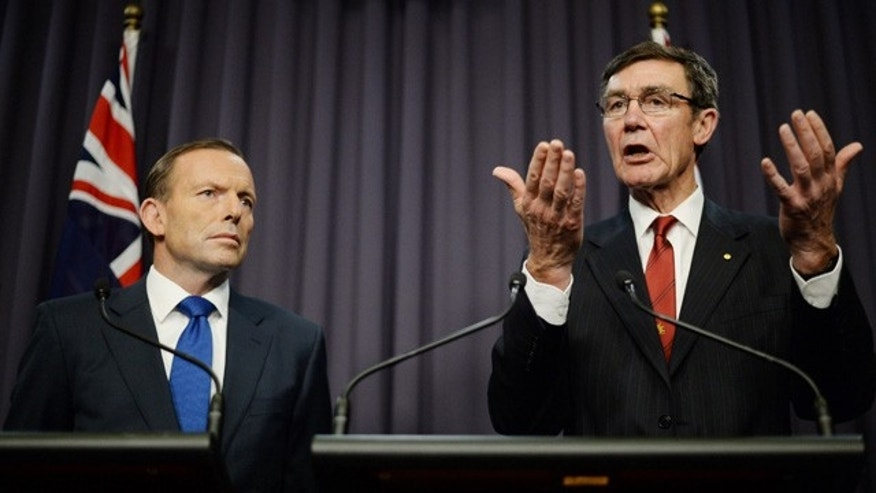 April 28, 2014: Australian Prime Minister Tony Abbott, left, looks on as retired Chief Air Marshall Angus Houston, the head of the Joint Agency Coordination Centre, speaks to the media during a press conference at Parliament House in Canberra. (AP Photo/AAP Image, Lukas Coch)