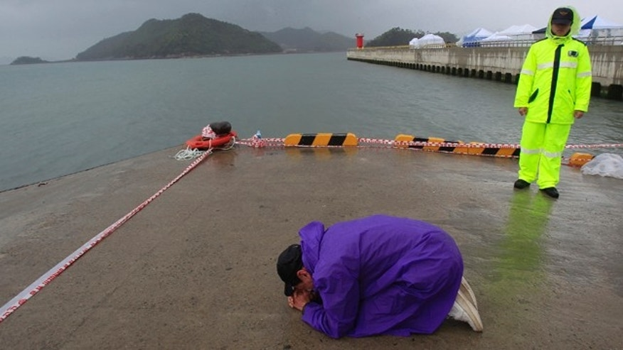 April 27, 2014: A relative of a passenger aboard the sunken Sewol ferry prays as he awaits news on his missing loved one at a port in Jindo, South Korea. (AP Photo/Ahn Young-joon)