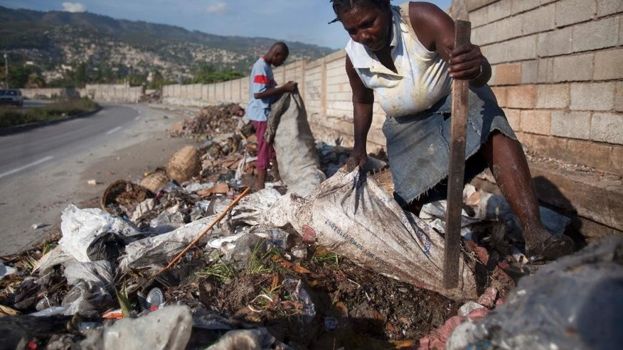 In this April 17, 2014 photo, Marie Satty, 52, digs through the trash littering the roadside for empty plastic bottles to sell to a recycling center in Carrefour, Haiti. Haiti's central government collects only about 40 percent of the capital's garbage, leaving the rest to pile up in streets and gutters, causing flooding when the rainy season comes. But now, through efforts of several entrepreneurial firms, more Haitians are learning how to recycle throwaways for cash. (AP Photo/Dieu Nalio Chery)