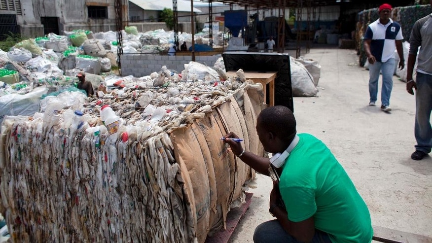 In this April 21, 2014 photo, a worker labels a bundle of plastic bottles at the Sustainable Recycling Solutions in Port-au-Prince, Haiti. The recycling center co-founded by Mike Shinoda of the rock band Linkin park recently received a grant from former President Bill Clinton's private foundation. (AP Photo/Dieu Nalio Chery)