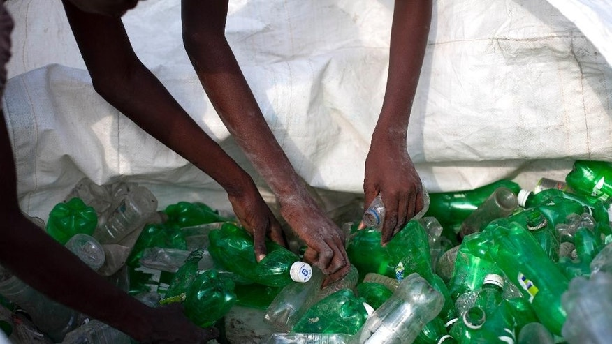 """In this April 16, 2014 photo, Danisa Julien and her sister Darlancia organize plastic bottles by color at a recycling center in Cite Soleil, Port-au-Prince, Haiti. The sisters take their recyclables to one of many kiosks run nationwide by a program called Ranmase Lajan, Haitian Creole for """"picking up money."""" (AP Photo/Dieu Nalio Chery)"""