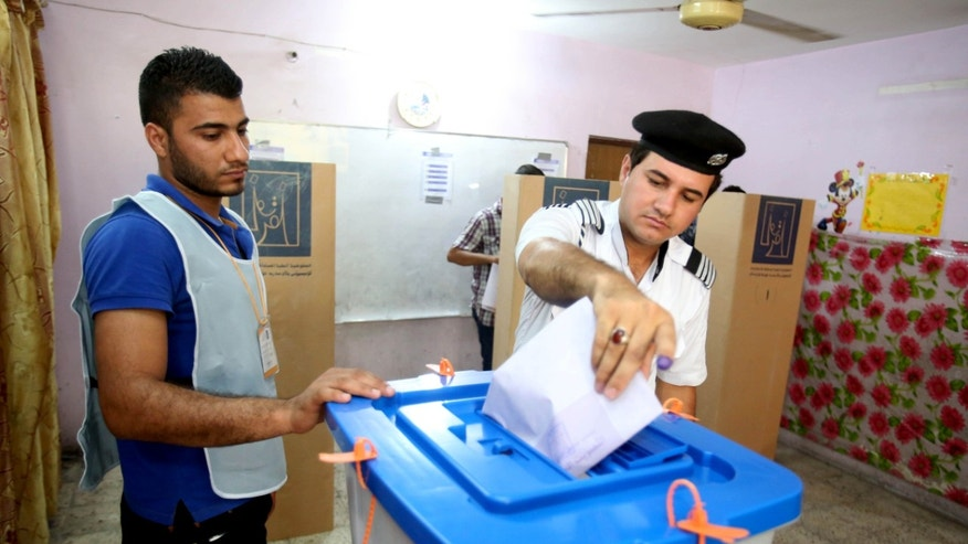 April 28, 2014 - An Iraqi traffic policeman casts his vote at a polling center in Baghdad, Iraq. Iraqi officials say suicide bombers have targeted polling centers as soldiers and security forces cast ballots ahead of parliamentary elections.