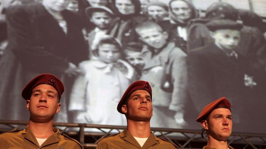 Israeli soldiers attend the opening ceremony of the Holocaust Remembrance Day at Yad Vashem Holocaust Memorial in Jerusalem, Sunday, April, 27, 2014. Israel's annual memorial day for the 6 million Jews killed in the Holocaust has begun with a ceremony marking 70 years since the Warsaw ghetto uprising. (AP Photo/Dan Balilty)