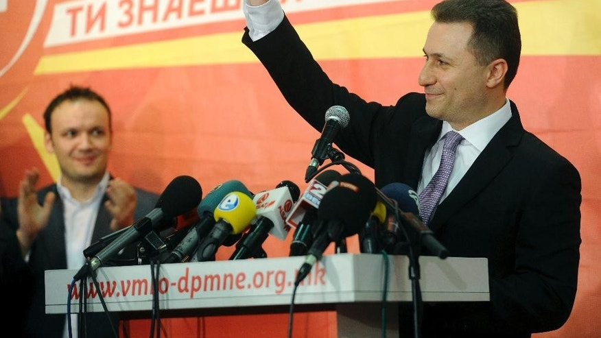 Macedonian Prime Minister and leader of the ruling conservative VMRO-DPMNE Nikola Gruevski greets his supporters while announcing a double victory in parliamentary and presidential elections, in Skopje, Macedonia, early Monday, April 28, 2014. Macedonia's incumbent prime minister claimed a landslide victory late Sunday in parliamentary and presidential elections, but the center-left opposition denounced what it called distorting interference in the democratic process by the ruling party and said it won't recognize the results. (AP Photo/Boris Grdanoski)
