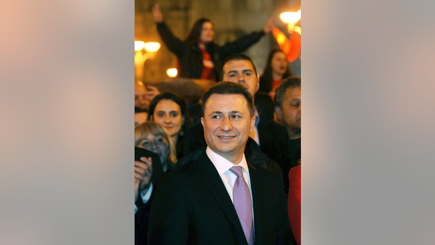 Macedonian Prime Minister and leader of the ruling conservative VMRO-DPMNE Nikola Gruevski, center, attends a celebration of the party's double victory in parliamentary and presidential elections, in downtown Skopje, Macedonia, early Monday, April 28, 2014. Macedonia's incumbent prime minister claimed a landslide victory late Sunday in parliamentary and presidential elections, but the center-left opposition denounced what it called distorting interference in the democratic process by the ruling party and said it won't recognize the results. (AP Photo/Boris Grdanoski)