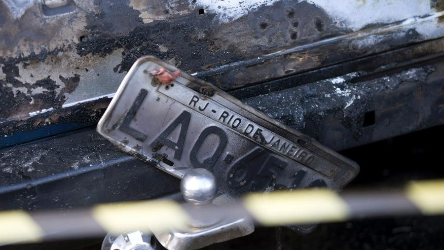 A charred car with Rio de Janeiro plates sits parked on the side of the street after protesters set several vehicles on fire to protest the death of an elderly woman who died yesterday during a police operation against suspected drug traffickers in the Complexo do Alemao in Rio de Janeiro, Brazil, Monday, April 28, 2014. The woman who died is Arlinda Bezerra das Chagas, age 72. (AP Photo/Silvia Izquierdo)