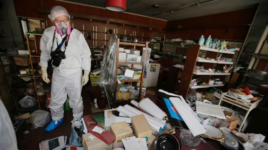 In this photo taken Thursday, April 17, 2014, Kazuhiro Onuki wearing white protective gear and a filtered mask stands in his ceramic and craft shop home in Tomioka, Fukushima Prefecture, northeastern Japan. There is no running water or electricity. Above all, radiation is everywhere. It's difficult to imagine ever living again in Tomioka, a ghost town about 10 kilometers (6 miles) from the former Fukushima Dai-ichi nuclear plant. And yet. More than three years after meltdowns at the plant forced this community of 16,000 people to flee, Onuki can't quite make the psychological break to start anew. (AP Photo/Shizuo Kambayashi)