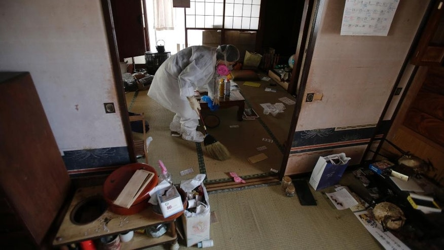 "In this photo taken Thursday, April 17, 2014, Michiko Onuki wearing white protective gear and a filtered mask cleans her home in Tomioka, a ghost town about 10 kilometers (6 miles) from the former Fukushima Dai-ichi nuclear plant in Fukushima Prefecture, northeastern Japan. ""The prime minister says the accident is under control, but we feel the thing could explode the next minute,"" said Onuki, who ran a ceramic and craft shop out of her Tomioka home. ""We would have to live in fear of radiation. This town is dead."" (AP Photo/Shizuo Kambayashi)"