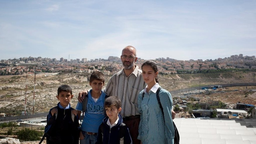 In this photo taken Monday, April 21, 2014, Ahmed Khatib poses with four of his six children along the separation barrier between the West Bank village of Hizme and the city of Jerusalem. The Khatibs are being kept apart by Israeli restrictions on Palestinian movement in east Jerusalem, including a towering separation barrier of cement slabs that cuts through families and neighborhoods. (AP Photo/Nasser Shiyoukhi)