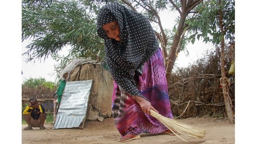 April 27, 2014: Ubah Mohammed Abdule, 33, center, sweeps the floor outside her hut as her son Abdullahi Yusuf Ahmed, 8, left, looks on in the Shedder refugee camp near the town of Jigjiga, in far eastern Ethiopia. (AP Photo/Elias Asmare)