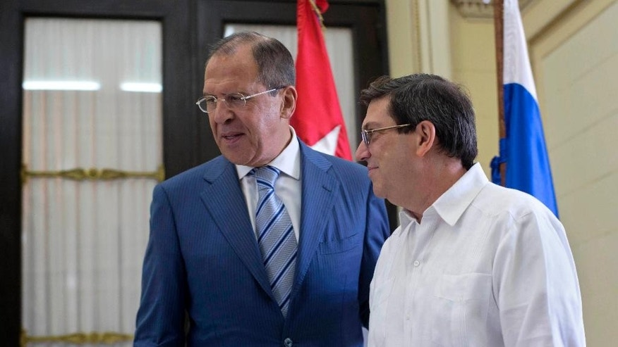 Cuba's Foreign Minister Bruno Rodriguez, right, walks with Russian's Foreign Minister Sergey Lavrov at the Foreign Ministry in Havana, Cuba, Tuesday, April 29, 2014. Lavrov is beginning his tour of Latin America in Cuba. (AP Photo/Ramon Espinosa)