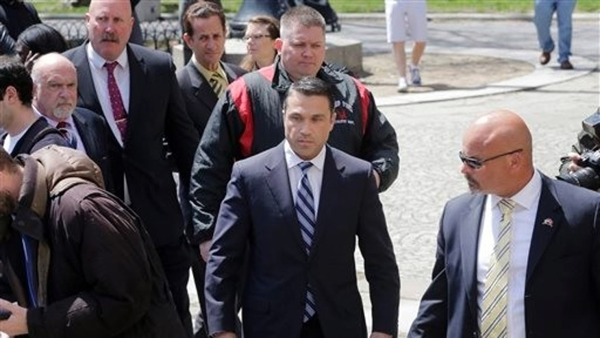 U.S. Rep. Michael Grimm, center, arrives for a news conference in a park next to federal court, Monday, April 28, 2014, in the Brooklyn borough of New York. The Staten Island Republican was arrested earlier in the day and pleaded not guilty to a 20-count federal indictment that includes charges of mail fraud, wire fraud and tax fraud. (AP Photo/Mark Lennihan)