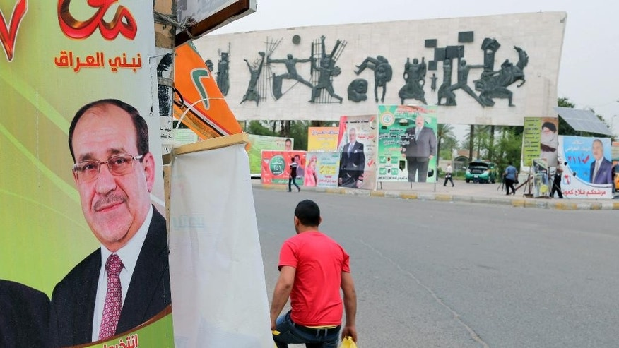 FILE - In this file photo taken on April 27, 2014 a man passes by a campaign poster of Iraqi Prime Minister Nouri al-Maliki in Baghdad, Iraq. If Iraqi Prime Minister Nouri al-Maliki wins a third four-year term in parliamentary elections Wednesday, he is likely to rely on a narrow sectarian Shiite base, only fueling divisions as Iraq slides deeper into bloody Shiite-Sunni hatreds. (AP Photo/Karim Kadim, File)