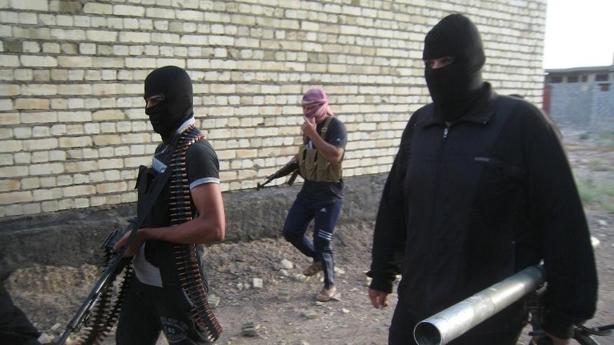 In this Monday, April 28, 2014 photo, masked anti-government gunmen move with their weapons as they patrol in Fallujah, Iraq. Al-Qaida-linked fighters and their allies seized the city of Fallujah and parts of the Anbar provincial capital Ramadi in late December after authorities dismantled a protest camp. Like the camp in the northern Iraqi town of Hawija whose dismantlement in April sparked violent clashes and set off the current upsurge in killing, the Anbar camp was set up by Sunnis angry at what they consider second-class treatment by the Shiite-led government. (AP Photo)