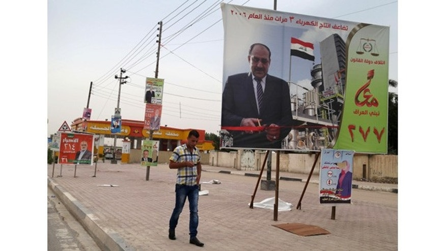 April 27, 2014: A man passes by a campaign poster of Iraqi Prime Minister Nouri al-Maliki in Basra, Iraq's second-largest city.  (AP)