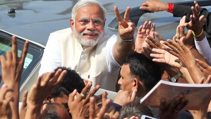 April 30, 2014: India's main opposition Bharatiya Janata Party's prime ministerial candidate Narendra Modi displays the victory symbol to supporters after casting his vote in Ahmadabad, India.  (AP)