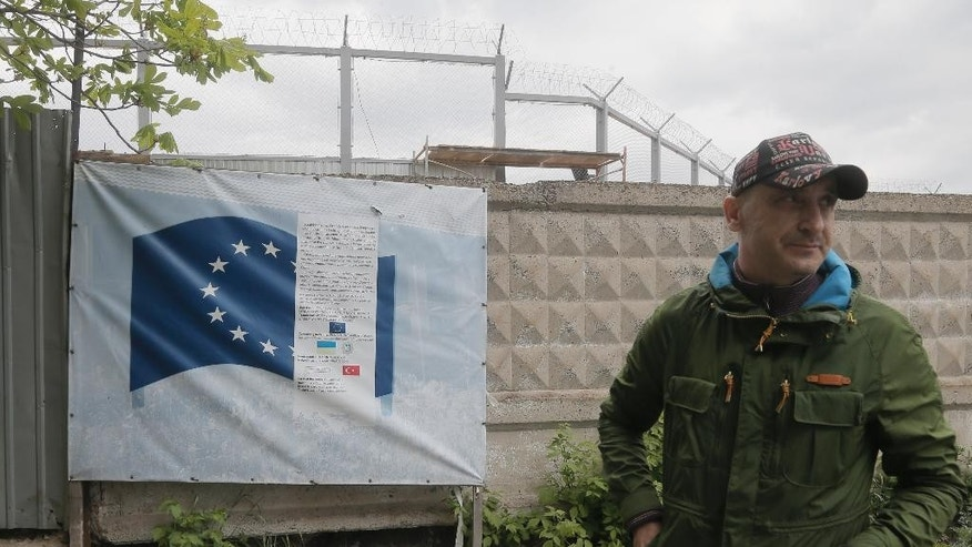 "In this photo taken Tuesday, April 29, 2014, deputy head of the construction site, Volodymyr Pashchenko, supervises work on the construction of a detention center in Zhdanivka, near Donetsk, Ukraine. Moscow calls the detention center under construction near the Russian border a ""fascist concentration camp."" Inside the barbed-wire fences, the reality is less ominous: It's an EU-funded project to hold asylum seekers and illegal immigrants, similar to countless detention centers across Europe. (AP Photo/Efrem Lukatsky)"