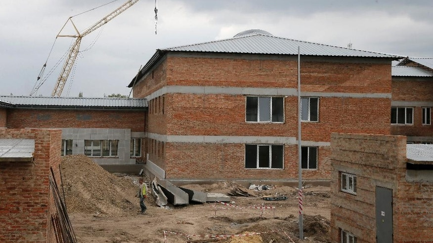 """In this photo taken Tuesday, April 29, 2014, a worker walks past a detention center under construction in Zhdanivka, near Donetsk, Ukraine. Moscow calls the detention center under construction near the Russian border a """"fascist concentration camp."""" Inside the barbed-wire fences, the reality is less ominous: It's an EU-funded project to hold asylum seekers and illegal immigrants, similar to countless detention centers across Europe. (AP Photo/Efrem Lukatsky)"""