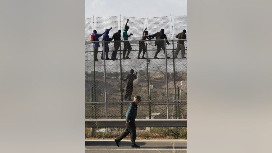 A Guardia Civil officer walks past sub-Saharan migrants standing on top of a metallic fence that divides Morocco and the Spanish enclave of Melilla, Thursday, May 1, 2014. Spain says around 700 African migrants have rushed its barbed wire border fences in the North African enclave of Melilla, and although police repelled most, 140 managed to enter Spanish territory. The migrants charged the fences in two waves, with 500 arriving in the early hours and another 200 later Thursday morning. Spain and Morocco stepped up border vigilance in Feb. when 15 migrants drowned trying to enter Spain's other north African coastal enclave, Ceuta. (AP Photo/Fernando Garcia)