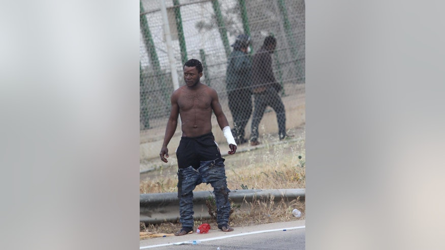 A sub-Saharan migrant stands on the Spanish soil after climbing a fence, as another is detained and sent back to the Moroccan side by Spanish Guardia Civil officers next to a metallic fence that divides Morocco and the Spanish enclave of Melilla, Thursday, May 1, 2014. Spain says around 700 African migrants have rushed its barbed wire border fences in the North African enclave of Melilla, and although police repelled most, 140 managed to enter Spanish territory. The migrants charged the fences in two waves, with 500 arriving in the early hours and another 200 later Thursday morning. Spain and Morocco stepped up border vigilance in Feb. when 15 migrants drowned trying to enter Spain's other north African coastal enclave, Ceuta. (AP Photo/Fernando Garcia)