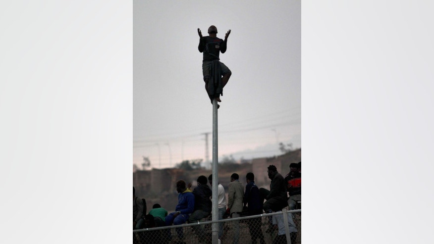 A sub-Saharan migrant prays siting on top of a pole set in a metallic fence that divides Morocco and the Spanish enclave of Melilla, Thursday, May 1, 2014. Spain says around 700 African migrants have rushed its barbed wire border fences in the North African enclave of Melilla, and although police repelled most, 140 managed to enter Spanish territory. The migrants charged the fences in two waves, with 500 arriving in the early hours and another 200 later Thursday morning. Spain and Morocco stepped up border vigilance in Feb. when 15 migrants drowned trying to enter Spain's other north African coastal enclave, Ceuta. (AP Photo/Fernando Garcia)