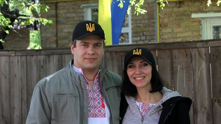 "FILE - In this April. 25, 2014 file photo, Natalia Snihur, 35, and her husband Yehor Korniyev, 35, pose for a photo in front of their home in Kiev, Ukraine, months after they protested with many others to help overthrow what they consider a corrupt, hardline pro-Russian president and bring a new pro-Western government to power.  Like many Ukrainians, Snihur and Korniyev are still proud of the popular uprising and hopeful that their country will turn into a dignified European nation, ""Ukraine is being born, it is in labor now, it is giving birth to a nation that will have a conscious national identity,"" Snihur said during an interview in her family kitchen. (AP Photo/ Maria Danilova, File)"